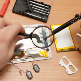 Master solder wires exploded tablet computer. He looks through a