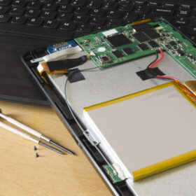 Process of PC Tablet Device Repair on a Wooden Table.